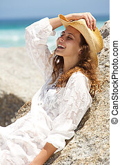 Smiling young woman with hat leaning against rock