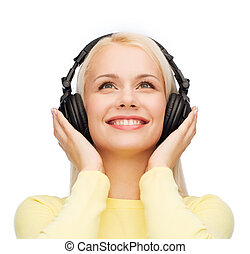 smiling young woman with headphones - music and technology ...