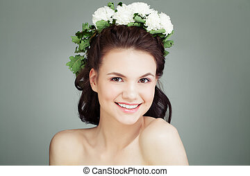 Smiling young woman with healthy skin and flowers on head, portrait