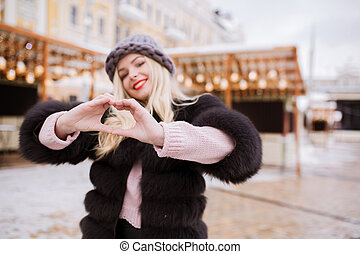 Smiling young woman with heart shaped hands posing on a backgriund of city lights