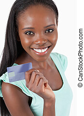 Smiling young woman with her new credit card against a white...