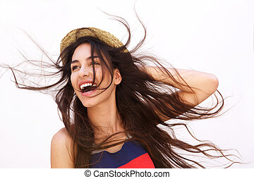 Smiling young woman with long hair blowing in the wind