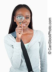 Smiling young woman with magnifier