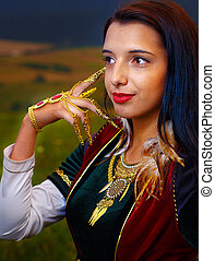 Smiling  Young woman with ornamental dress and hand jewel. Natural background.