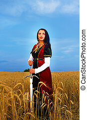 Smiling Young woman with ornamental dress and sword in hand  standing on a wheat field with sunset. Natural background