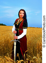 Smiling Young woman with ornamental dress and sword in hand  standing on a wheat field with sunset. Natural background..