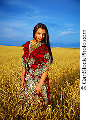 Smiling Young woman with ornamental dress standing on a wheat field with sunset. Natural background and blue sky