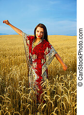 Smiling Young woman with ornamental dress standing on a wheat field with sunset. Natural background and blue sky.