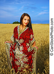 Smiling Young woman with ornamental dress standing on a wheat field with sunset. Natural background