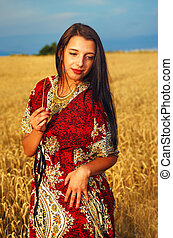 Smiling Young woman with ornamental dress standing on a wheat field with sunset. .