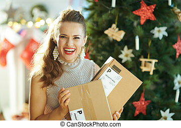smiling young woman with parcels near Christmas tree