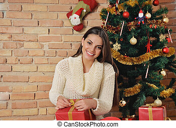 smiling young woman with present box on Christmas tree background