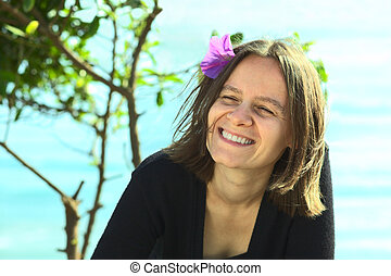 Smiling young woman with purple flower in her hair on a sunny day on the coast (Selective Focus, Focus on the left eye)
