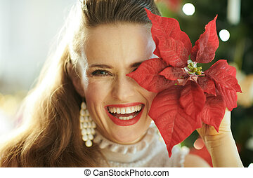 smiling young woman with red poinsettia near Christmas tree