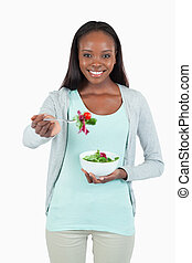 Smiling young woman with salad