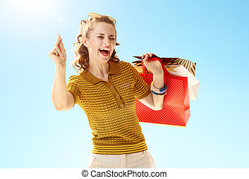 woman with shopping bags fingers snapping against blue sky