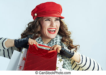 smiling young woman with shopping bags looking at copy space