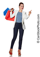 Smiling young woman with shopping bags pointing on copy space
