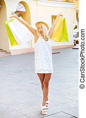Smiling young woman with shopping bags on the street -...