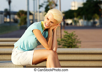 Smiling young woman with short blond hair sitting outside