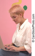 Smiling young woman with short dyed blond hair typing on a laptop. She wears mom jeans and dress shirt. Over pink wall