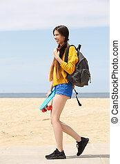 Smiling young woman with skateboard by beach