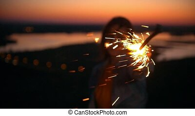 Smiling young woman with sparkler at summer sunset on the...