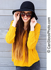 Smiling young woman with sunglasses outside