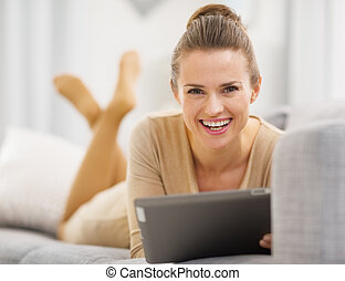Smiling young woman with tablet PC laying on sofa