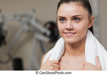 Smiling young woman with towel around neck in gym