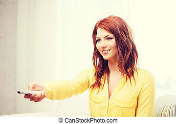 smiling young woman with tv remote control at home