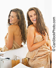 Smiling young woman with wet hair in bathroom