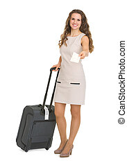 Smiling young woman with wheels suitcase giving air ticket