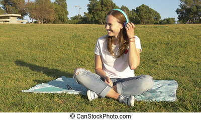 Smiling young woman with wireless headphones seat on green grass