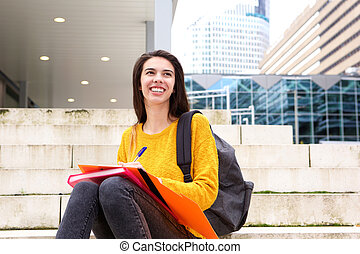 Smiling young woman writing in notebook