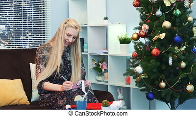 Smiling young woman writing letter near the xmas tree on the New Year's Eve