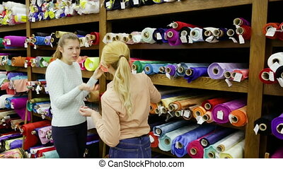 Smiling young women shopping together in fabric shop, choosing textiles for dressmaking