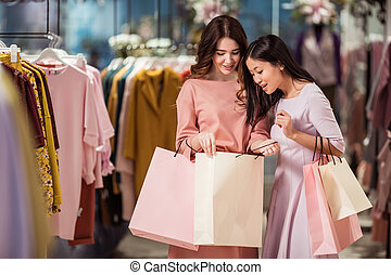Smiling young women with shopping bags