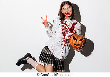 Smiling zombie woman covered in blood stains