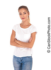 smilling and confident young casual woman standing with arms folded