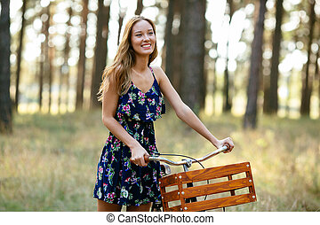 Smilling girl with a bicycle in the forest.