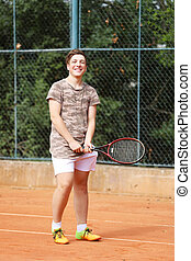 Smilling young boy on tennis court