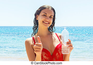 Smilling young woman in a red swimsuit is holding a bottle of water and showing thumb-up at the sea background