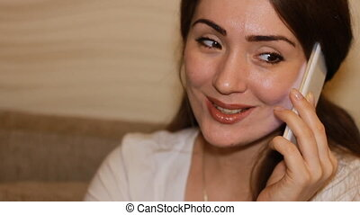 Smilling young woman talks on a mobile phone and says I love...