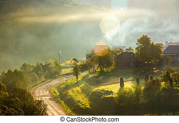 smoke and fog over the village at sunrise. beautiful rural...