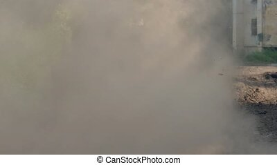 Smoke and mud from dirty caterpillar tracks on military tank...