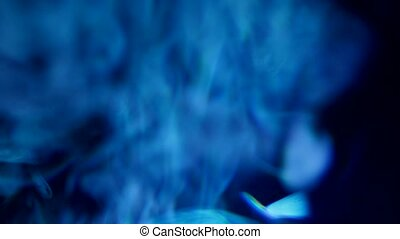 Smoke and mysterious blue light from cinema projector in...