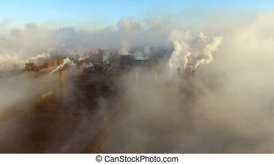 Smoke and soot is emitted from the factory pipes of the ...