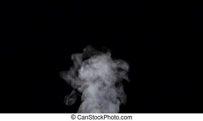 Smoke billowing over steady flow on black background, slow motion