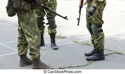 Smoke break - Armed militaries having a smoke break, their...